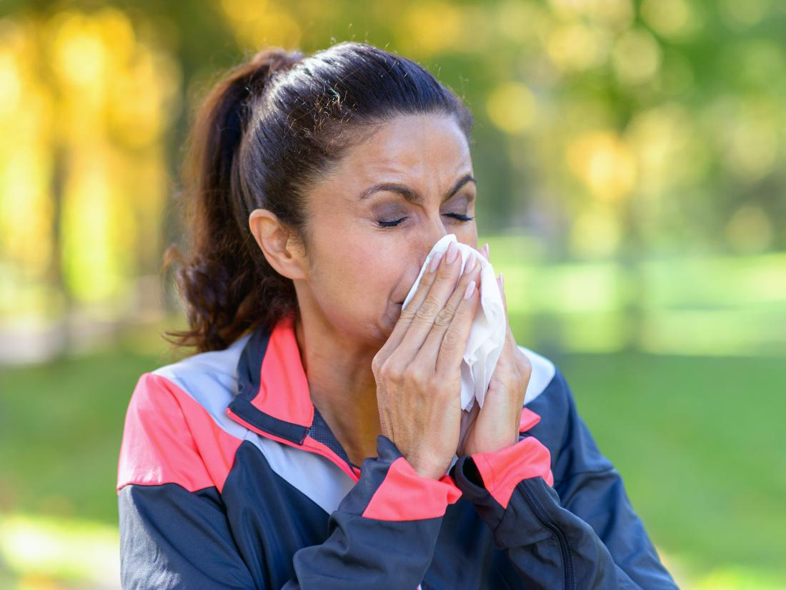a woman blowing her nose as she is Working out while sick