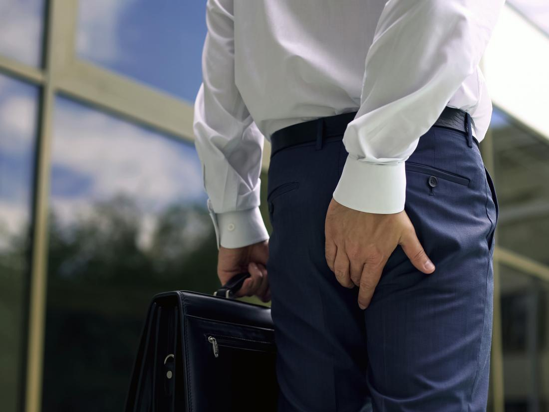 a business man touching his bum because he is experiencing butt sweat.