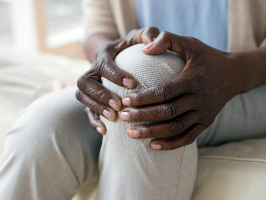 a woman holding her knee because of burning pain.