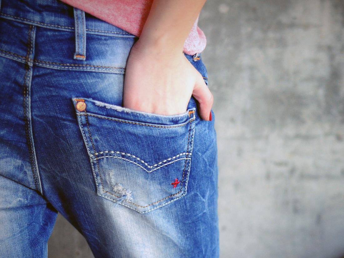 a woman with her hand in her back pocket because her bum is itchy from a anal yeast infection.