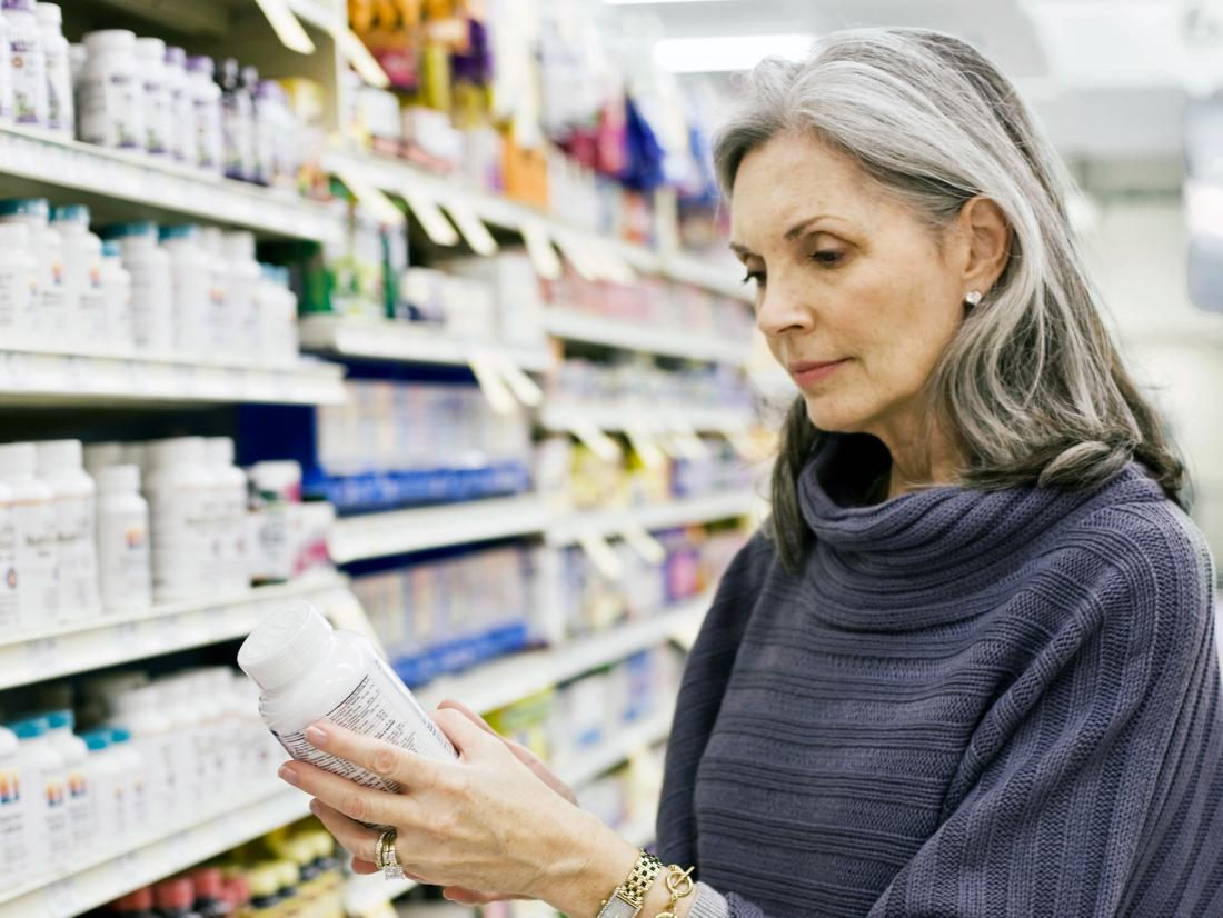 a woman in a pharmacy looking at supplements for neuropathy