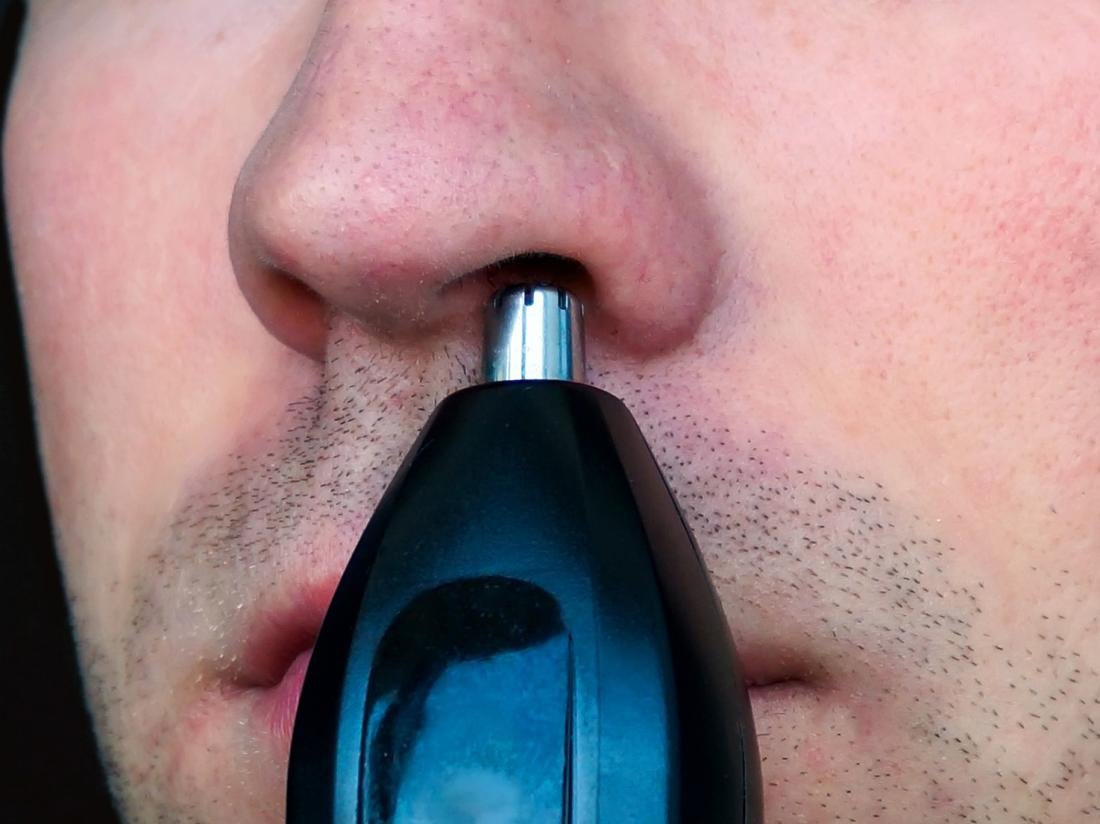 a man using a trimmer as a nose hair removal device
