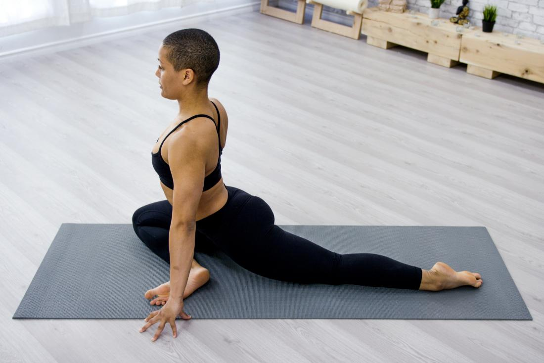 a woman doing a pigeon pose as part of her hip external rotation routine