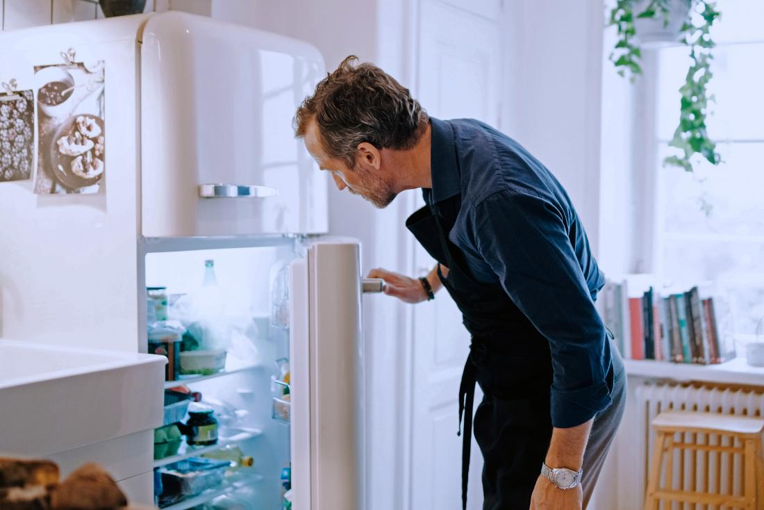 a man looking in the fridge for Crohn's snacks