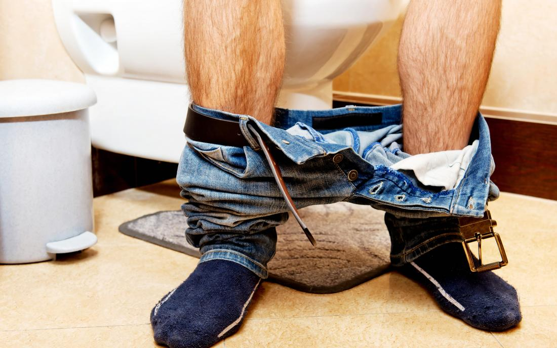 a man sat on the toilet that may have constipation that is an emergency