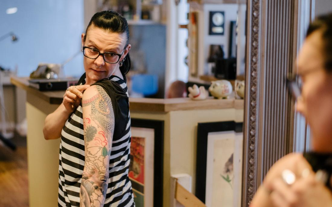 a woman looking at her tattoo because it's itchy.