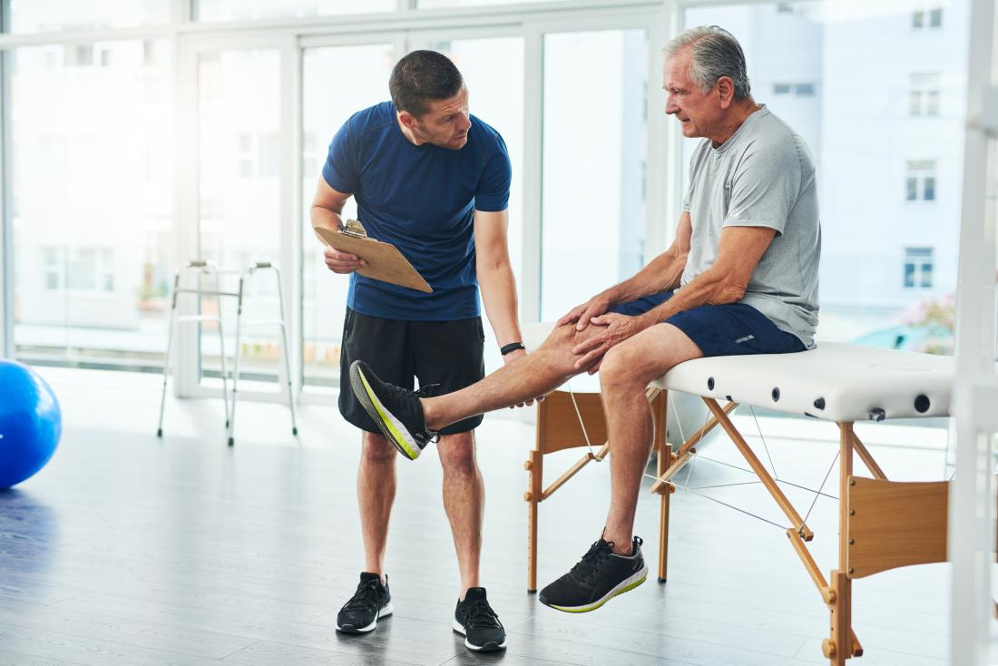 physiotherapist working with older man