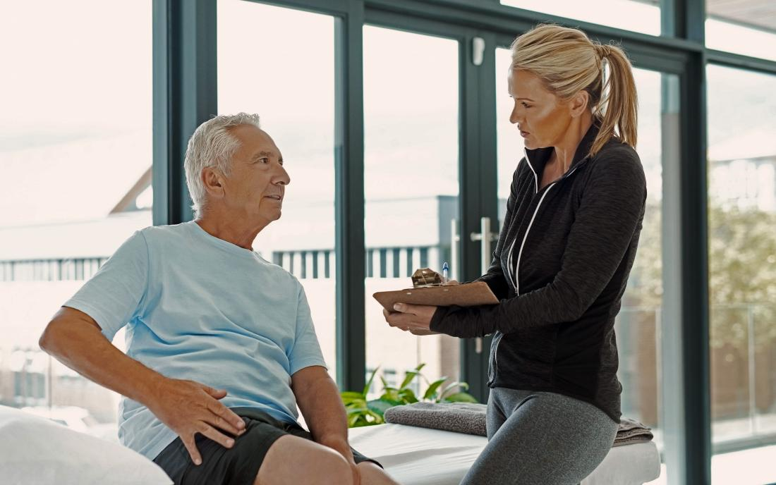 a man talking to a physical therapist about treatment for his hip osteoarthritis
