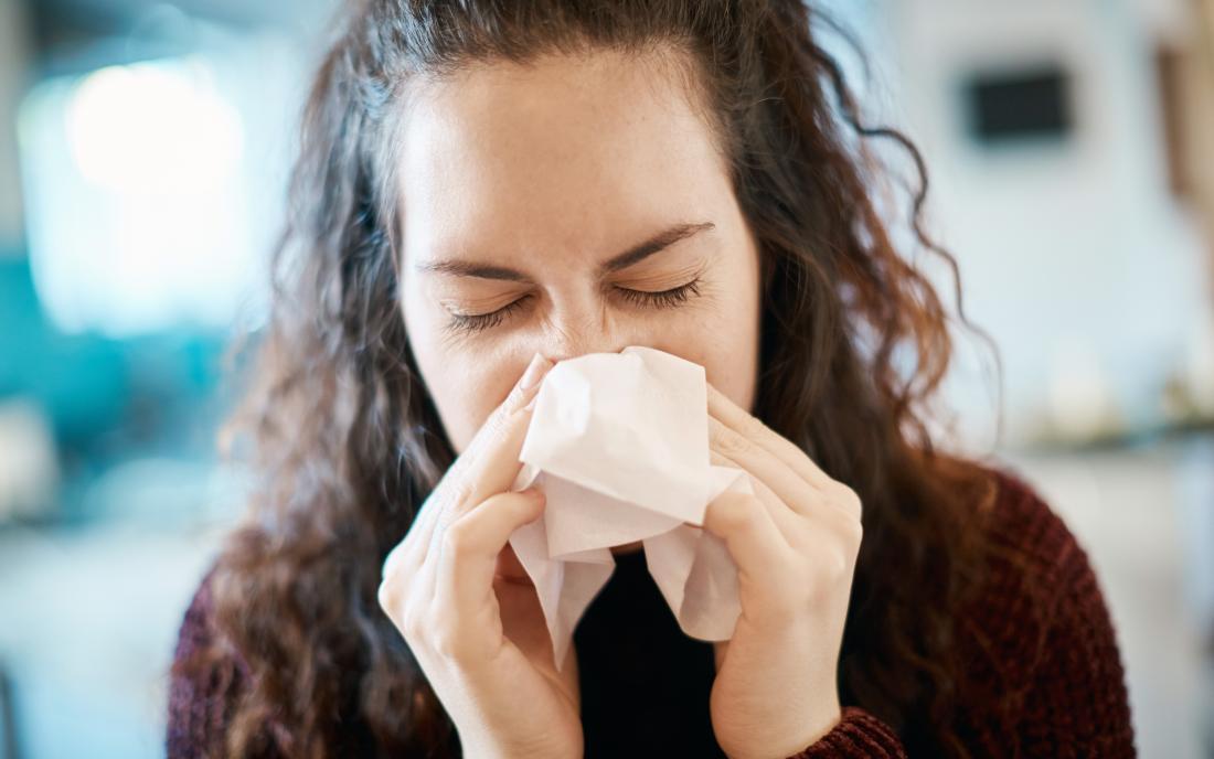 a woman suffering a nosebleed and headache.