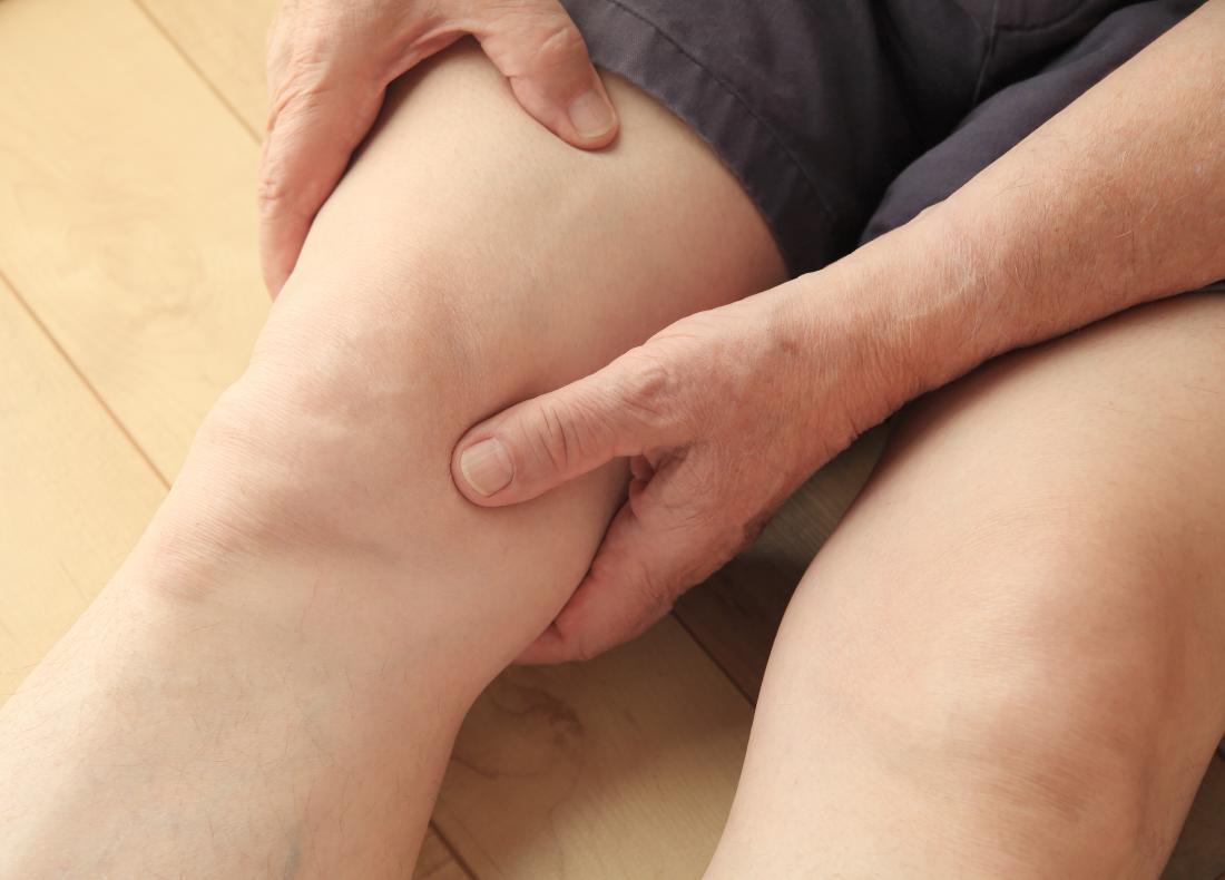 a man feeling his leg to check for hair loss.
