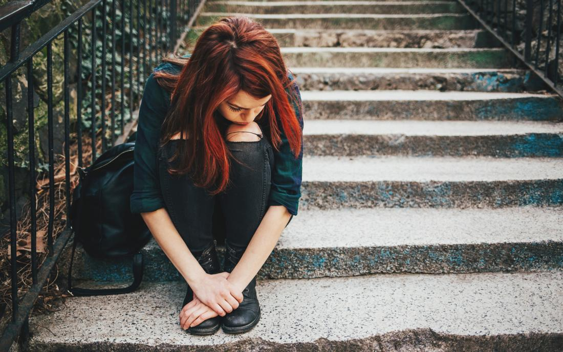 Sad lonely girl sitting on stairs because of emotional abuse