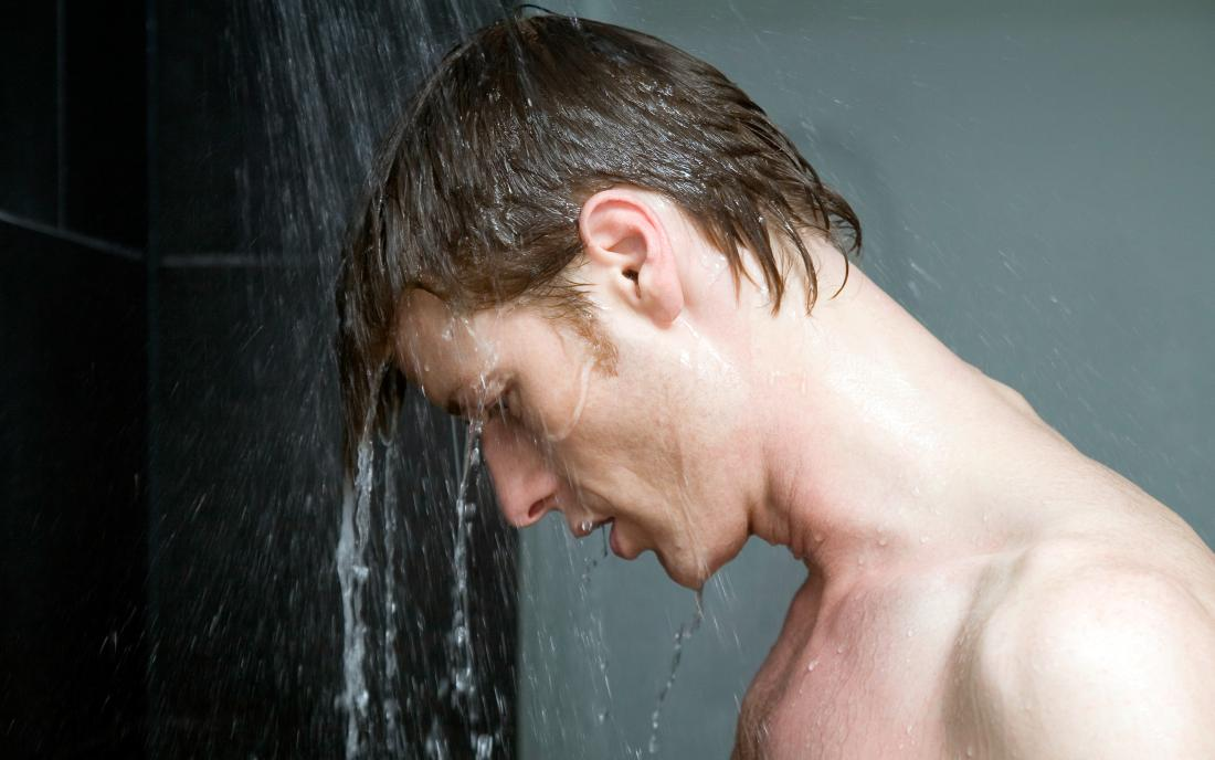 a man looking down in the shower to see that he has a loss of pubic hair.