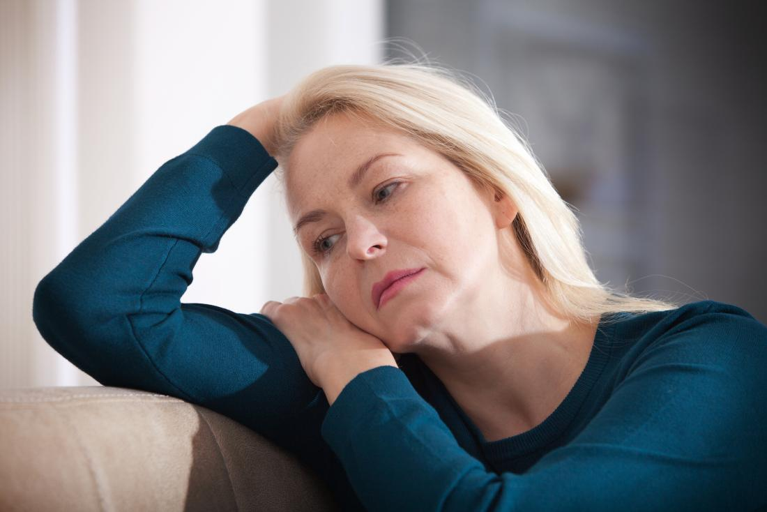 a woman sat on a sofas looking worried as she has high blood pressure and anxiety
