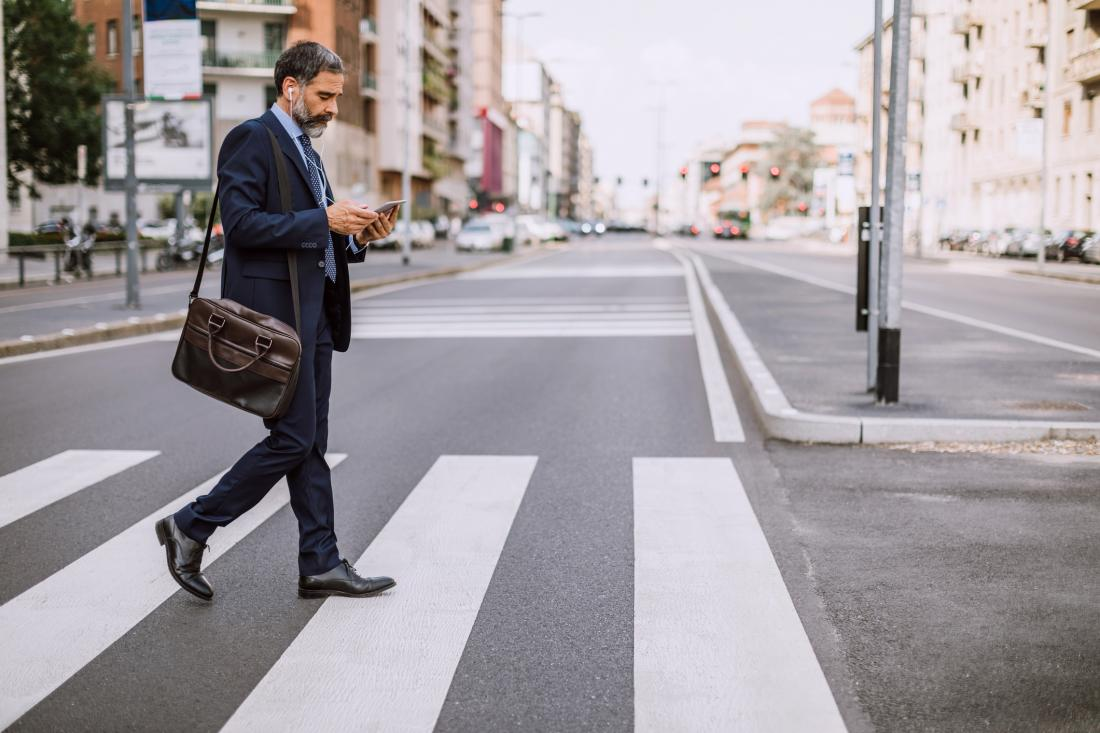 man crossing zebra while texting