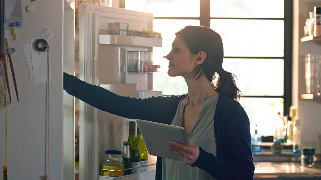 a woman looking in the fridge for food that may help in her heavy metal detox