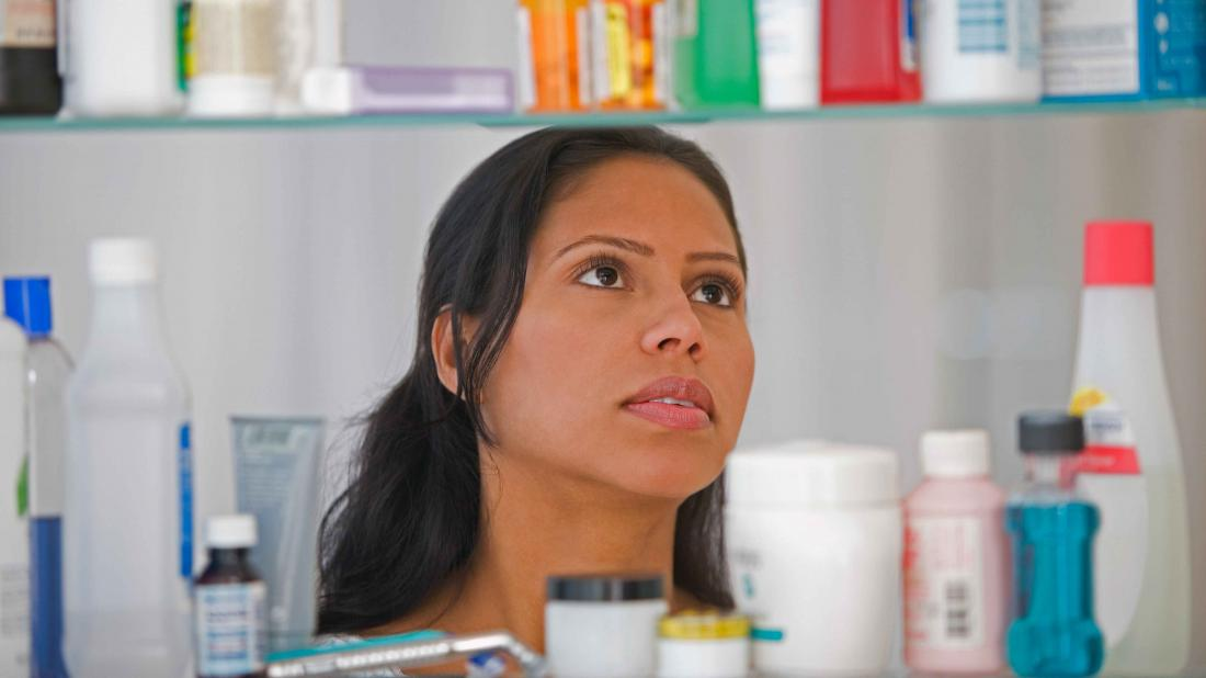 a woman looking in a medicine cabinet to see which medication need disposal