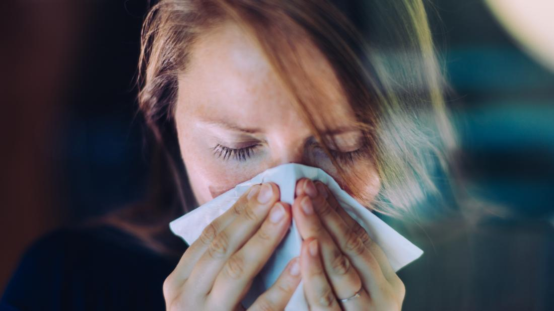a woman experiencing a runny nose because of the early stages of a cold