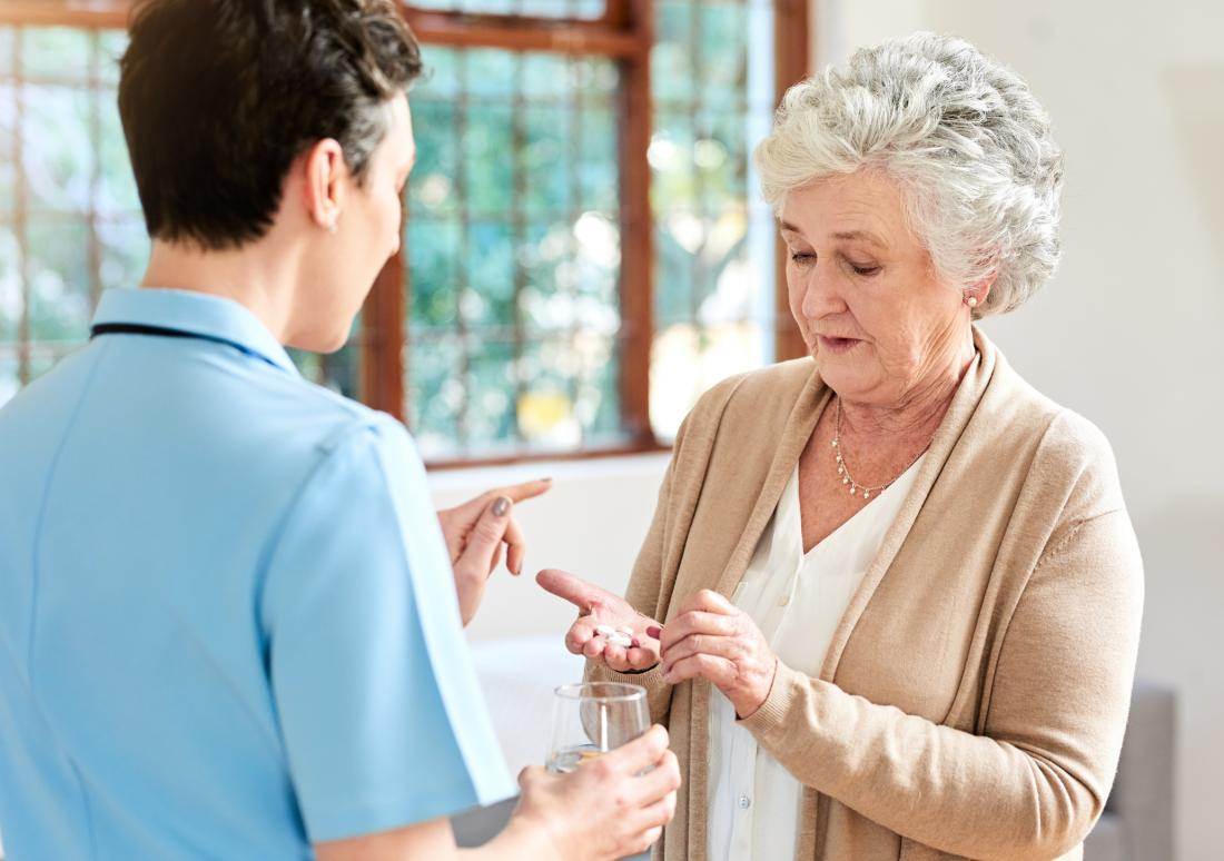 nurse giving drugs to senior lady