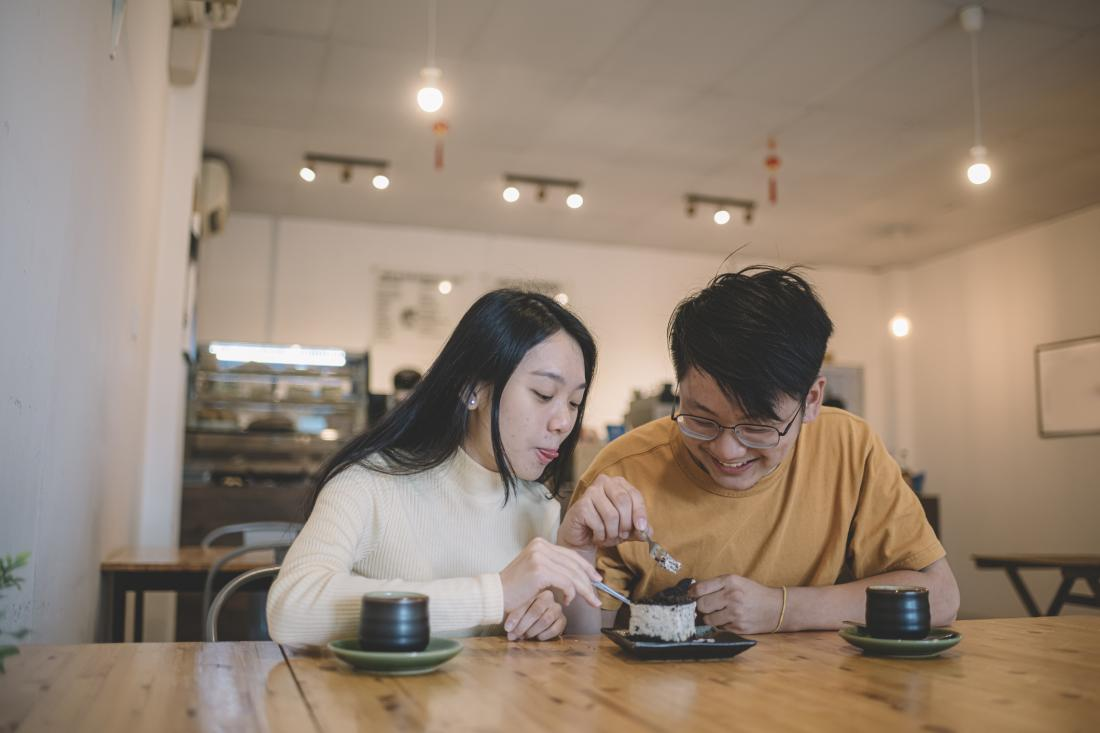 two people eating a piece of cake