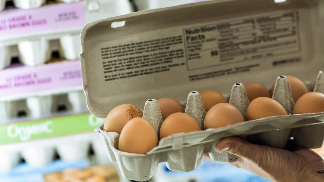 a person holding a box of eggs that may be cage free free range or pasture raised