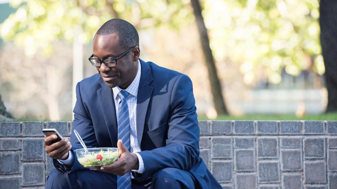 a man eating a salad for lunch as part of this 16:8 intermittent fasting diet