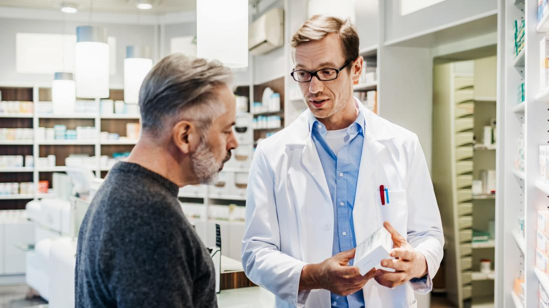 a man talking to a pharmacist about medications that can be used as Ibs treatment