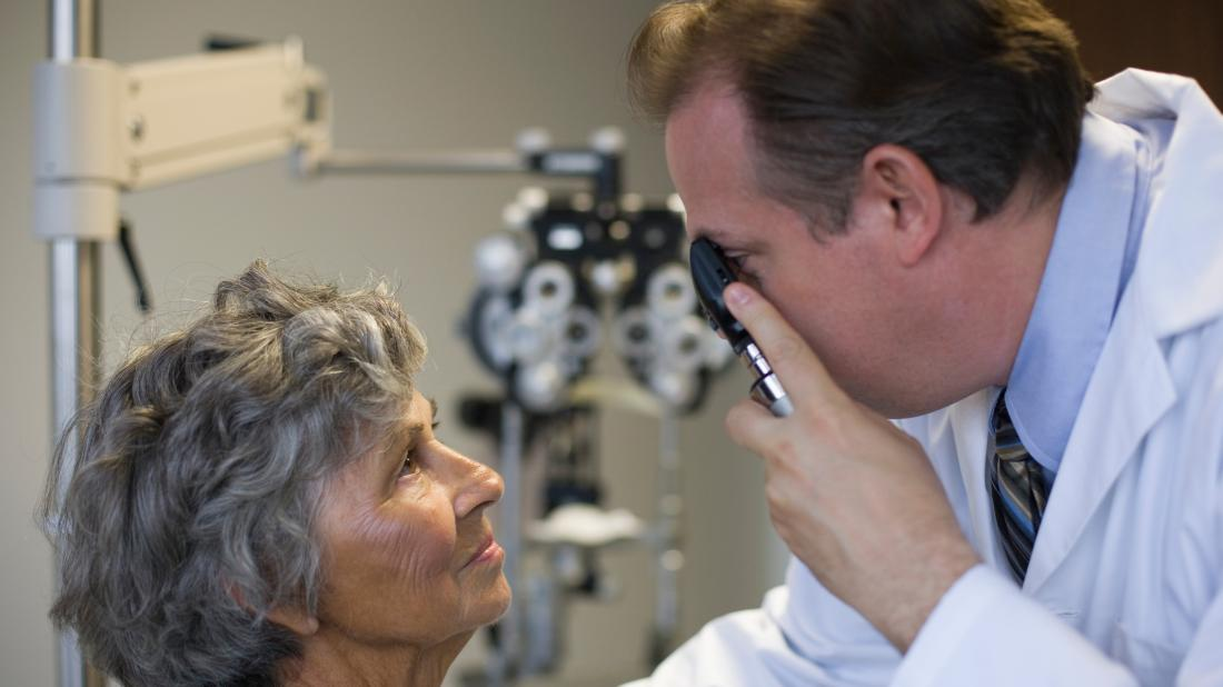 a doctor checking a persons eyes for any conditions related to Crohn's disease