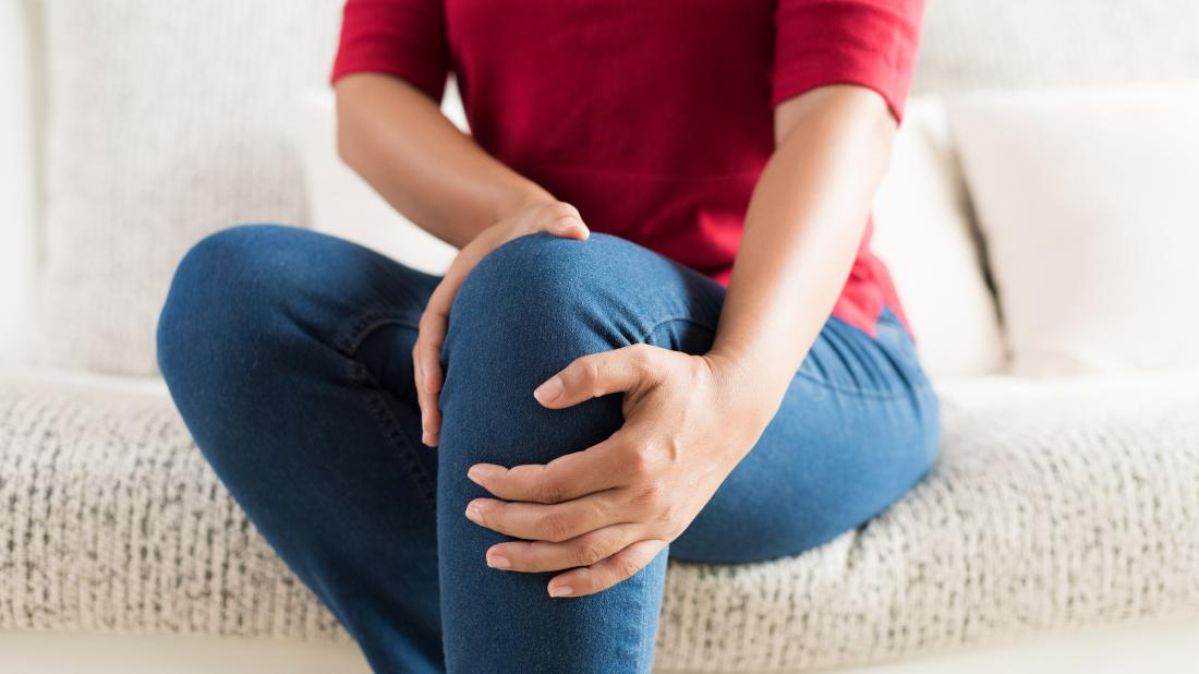 a woman holding her knee because she has leg pain and not chest pain.