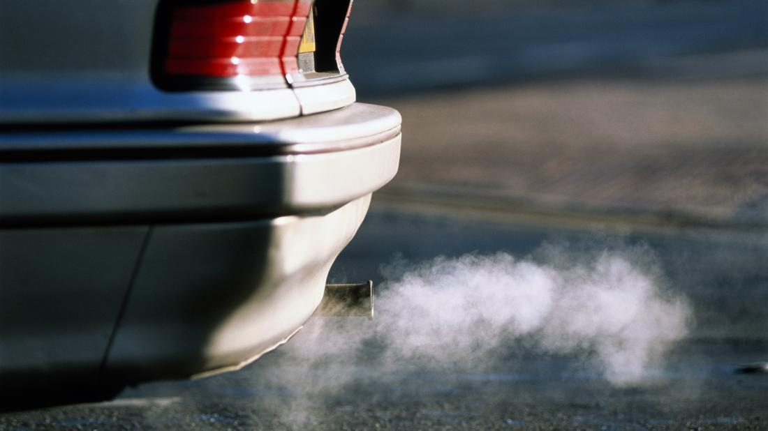 air pollutants coming out of a car exhaust pipe that may have negative health effects on the body