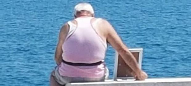 El hombre lleva la fotografía de su difunta esposa a ver el mar.