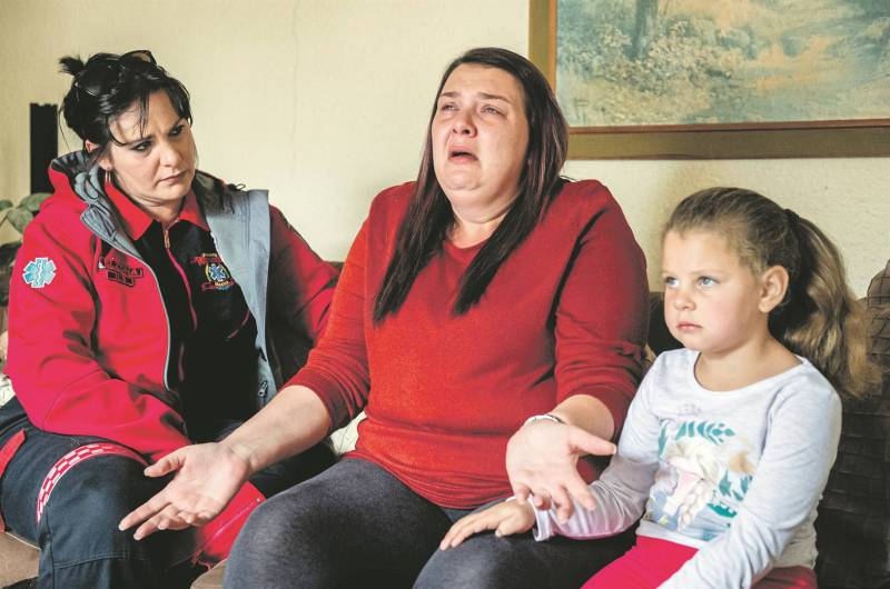 Elzona Meyer, a paramedic, consoles Rhödine de Beer, whose 11-year-old son, Pedré, was electrocuted on Monday. With them is Pedré's sister, Anelé, 5.