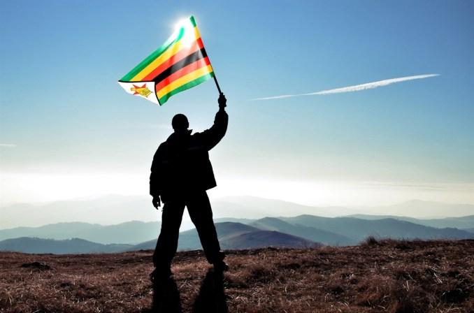 Successful silhouette man winner waving Zimbabwe f