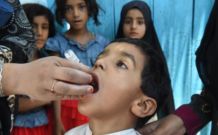 Health worker administers oral polio vaccine to child in Quetta, Pakistan