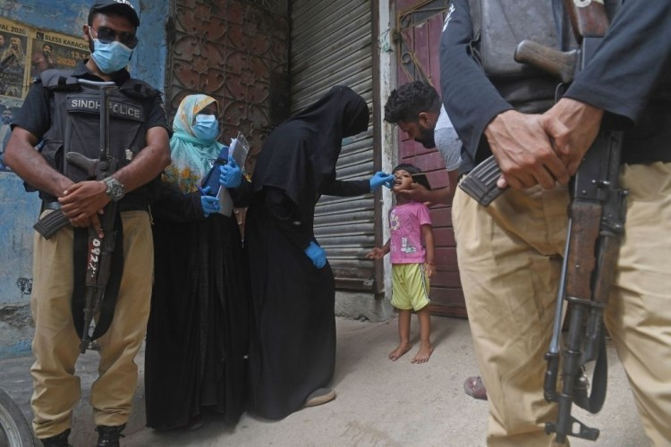 Policemen stand guard as a health worker administers polio vaccine