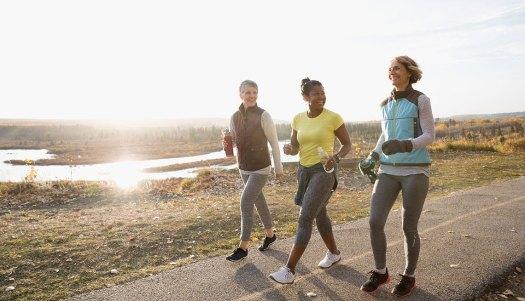Women power walking exercising on sunny path in autumn park