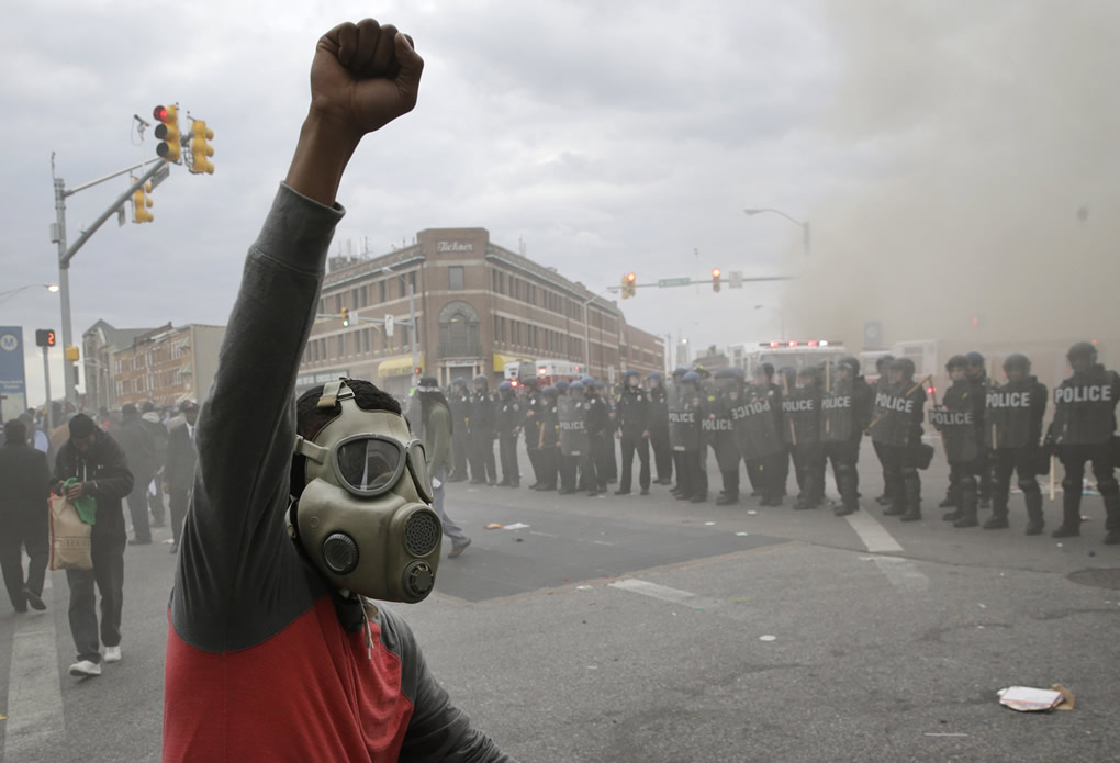 A demonstrator raises his fist as police stand in formation as a store burns, Monday, April 27, 2015, during unrest following the funeral of Freddie Gray in Baltimore. <span class=meta>AP Photo/Patrick Semansky</span>
