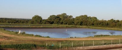 square body of water surrounded by a fence