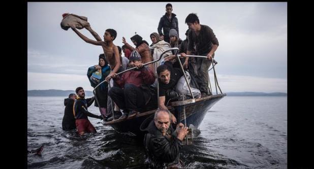 لاجئون على سواحل اليونان وقارب مكتظ يجسد أزمة اللاجئين الأوروبية
