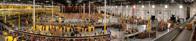 Photo of a panorama image of an Amazon logistics center, where people are packaging products in boxes.