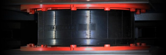 A thick cylinder of rubber sandwiched between two red steel plates.