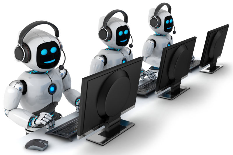Three robots sitting in front of computers and wearing phone headsets.