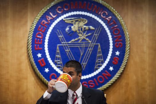 FCC Chairman Ajit Pai drinking from a giant coffee mug in front of an FCC seal.