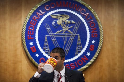 Ajit Pai with at FCC with oversize coffee mug