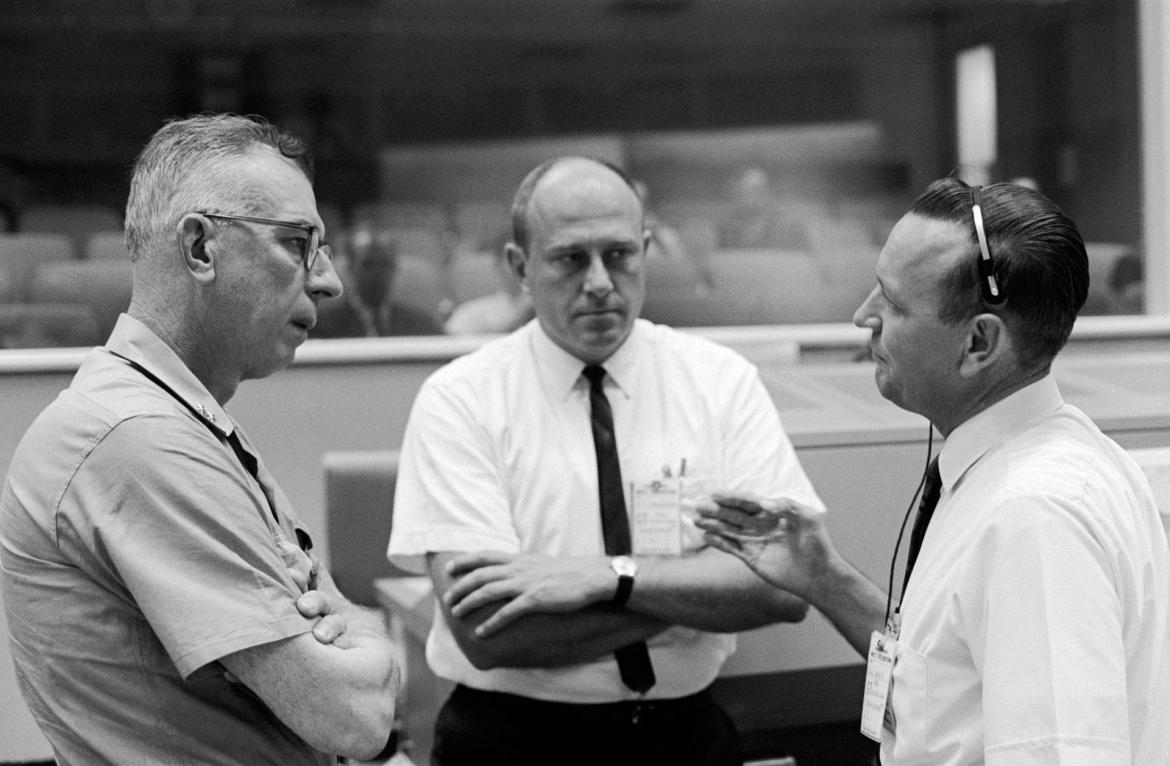 In 1965, Rear Admiral W.C. Abhau (left), is shown in the Mission Control Center with Bob Thompson (center) and Chris Kraft, flight director for Gemini-5.