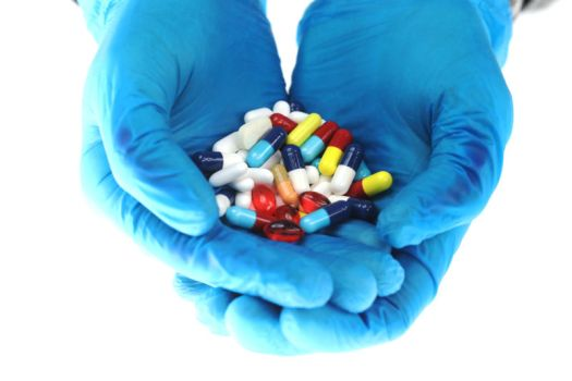 Hands wearing blue surgical gloves hold brightly colored medications, including antibiotics.