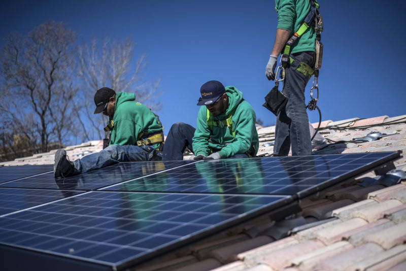 Workers secure solar panels to a rooftop during a SolarCity Corp. residential installation in Albuquerque, New Mexico, on Monday, February 8, 2016.