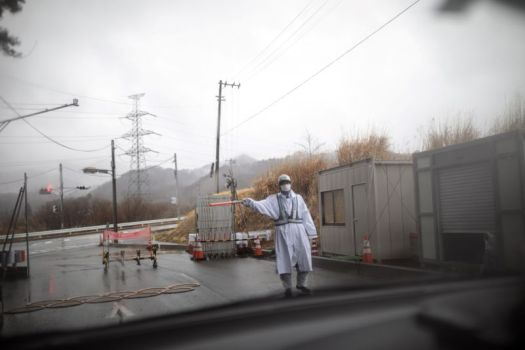 Man in protective gear gesturing outside Fukushima prefecture