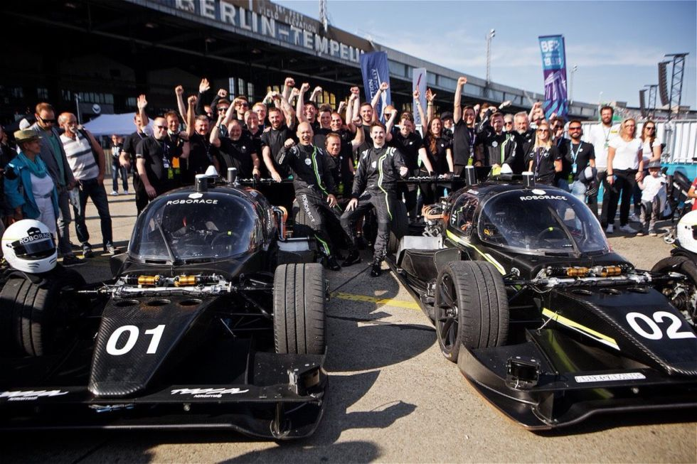 The Roborace teams celebrate after the first successful human+machine race.