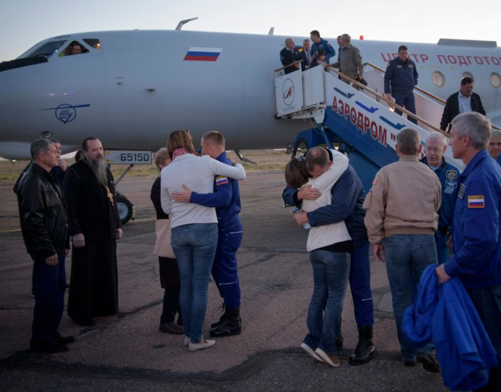 Astronaut Nick Hague, right, and cosmonaut Alexey Ovchinin, left, embrace their families after landing in Baikonur, Kazakhstan, on Thursday.