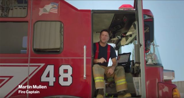 A firefighter sitting in a fire truck and talking.
